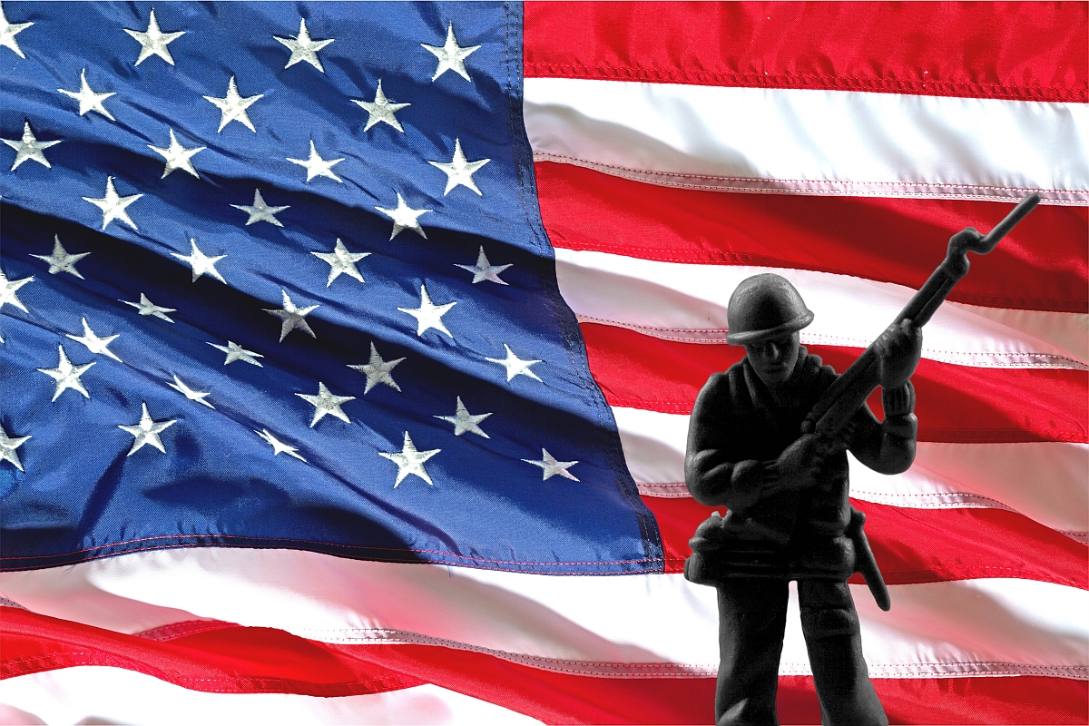 Soldier in front of an American flag.